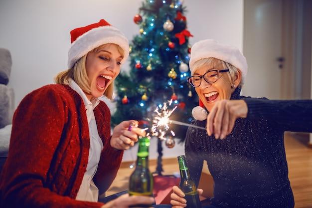 Glückliche schöne kaukasische blonde frau, die wunderkerze aufhellt und bier hält. ihre mutter hält wunderkerze und bier. beide haben weihnachtsmützen auf gehört. familienzeit.