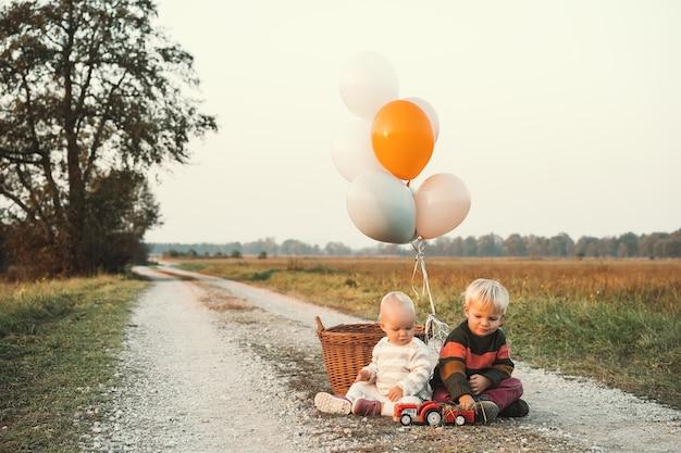 Glückliche schöne kinder, die auf der natur spielen bruder und schwester im herbstpark familie im freien