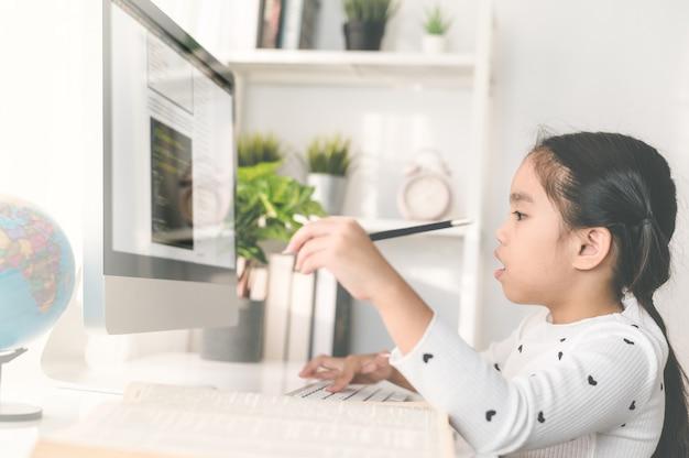 Glückliche schöne kleine studentin, die einen computer verwendet, um durch on-line-e-learning zu studieren