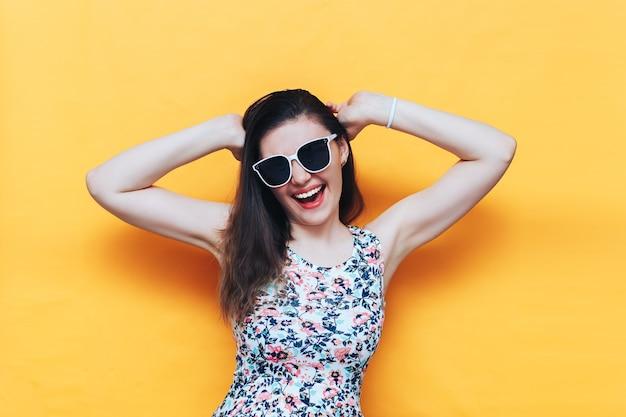 Glückliche schöne lachende yound frau im kleid und in der weißen sonnenbrille