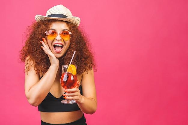 Glückliche schöne lockige frau im sommer lässige kleidung mit einem glas cocktail trinken studio schuss isoliert