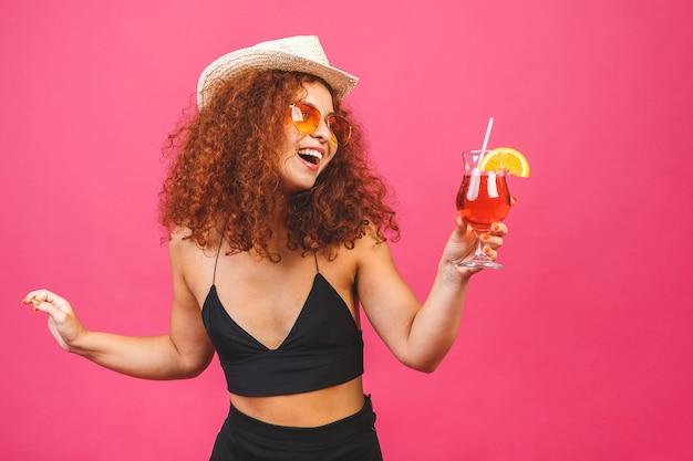 Glückliche schöne lockige frau im sommer lässige kleidung mit einem glas cocktailgetränk