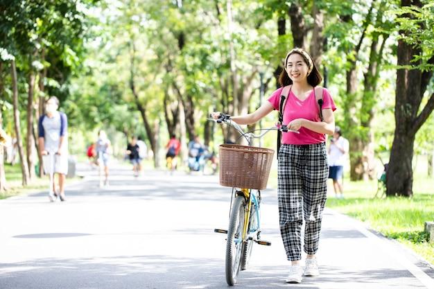 Glückliche schöne mädchen, die fahrräder draußen führen, genießen moment im öffentlichen park