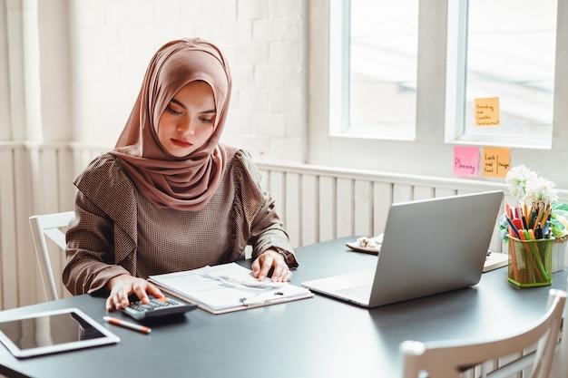 Glückliche schöne moslemische geschäftsfrau, die über finanzielles mit geschäftsbericht und taschenrechner im innenministerium arbeitet.