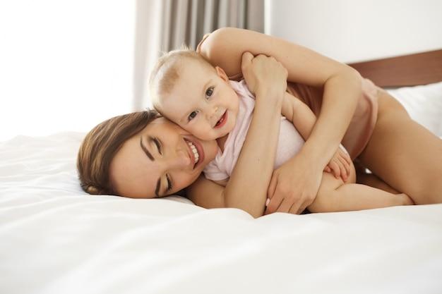 Glückliche schöne mutter in nachtwäsche, die auf bett mit ihrer kleinen tochter liegt, die lächelnd umarmt.