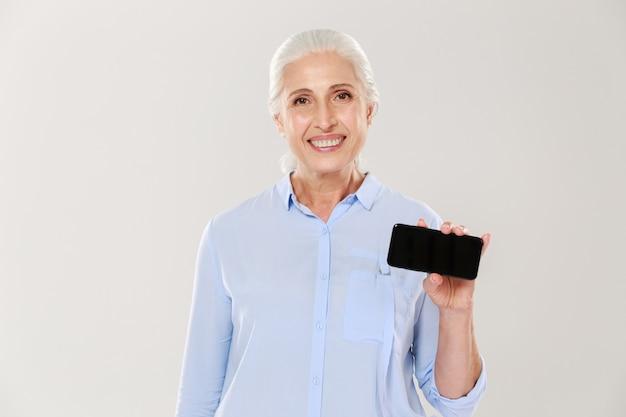 Glückliche schöne reife frau, die smartphone mit leerem schwarzen bildschirm lokalisiert zeigt