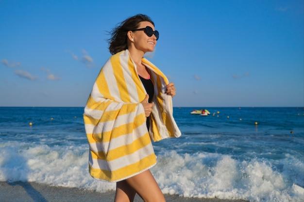 Glückliche schöne reife frau im badeanzug mit strandtuch, das entlang der küste geht
