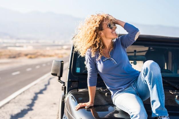 Glückliche schöne reife frau mit sonnenbrille, die mit der hand im lockigen haar posiert, während sie auf der motorhaube des jeeps auf der autobahn sitzt. fröhliche, stilvolle frau, die während ihres roadtrips auf der motorhaube am straßenrand posiert