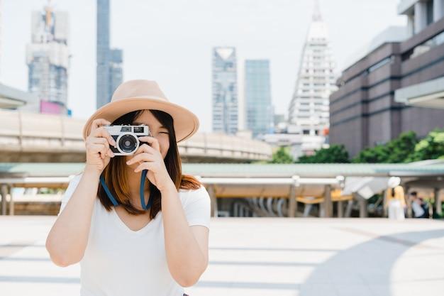 Glückliche schöne reisende asiatische frau trägt rucksack