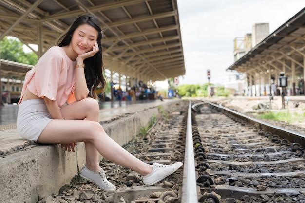Glückliche schöne reisende schließen ihre augen, während sie auf den zug am bahnhof warten, der in der nähe der eisenbahn sitzt.
