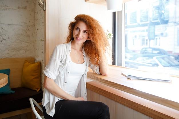 Glückliche schöne rothaarige junge dame, die im café sitzt