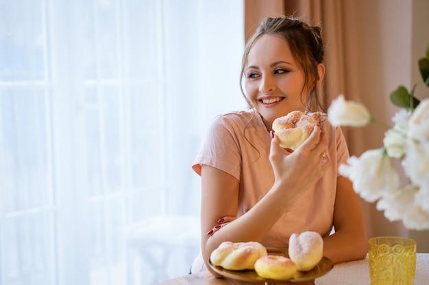 Glückliche schöne schwangere frau, die am tisch sitzt und einen kuchen hält