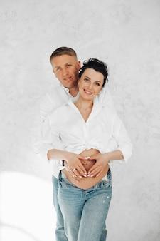 Glückliche schöne schwangere frau, die lächelt, während sie von einem mann von hinten umarmt wird