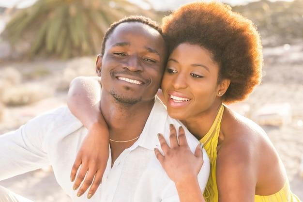 Glückliche schöne schwarze rasse afrikanisches paar in liebe oder freundschaft bleiben zusammen, umarmt mit großen smilies unter dem sonnenlicht des sommers im urlaub oder lebensstil in ihrer stadt