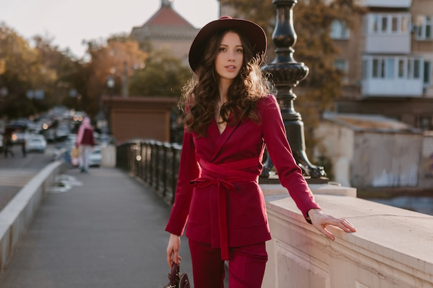 Glückliche schöne stilvolle frau im lila anzug, der in stadtstraße, frühlingssommer-herbstsaison-modetrend trägt hut trägt und geldbörse hält