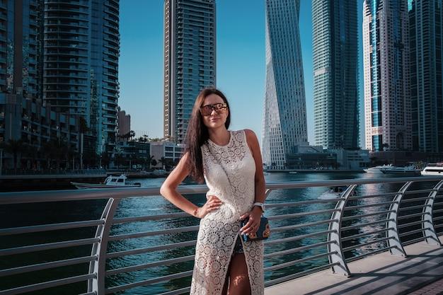 Glückliche schöne touristische frau im dubai-jachthafen