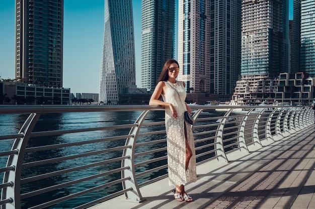 Glückliche schöne unerkennbare touristenfrau im modischen weißen sommerkleid, das in dubai genießt
