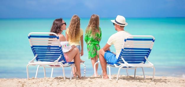 Glückliche schöne vierköpfige familie am strand. eltern, die auf sunbed sich entspannen und kinder, die spaß auf der küste haben