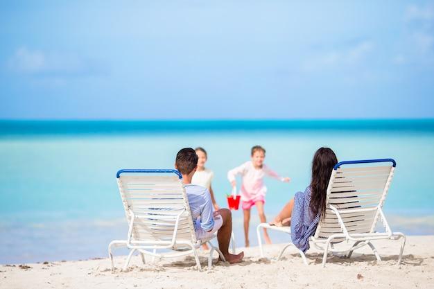 Glückliche schöne vierköpfige familie am strand. eltern entspannen sich auf der sonnenliege und kinder haben spaß an der küste