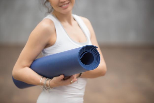 Glückliche schöne yogifrau, die ihre matte, abschluss hochhält