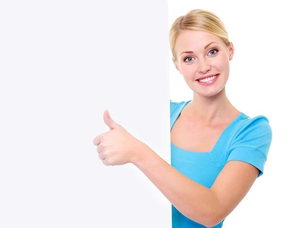 Glückliche schöne zahnig lächelnde frau schaut aus dem banner heraus und zeigt daumen hoch