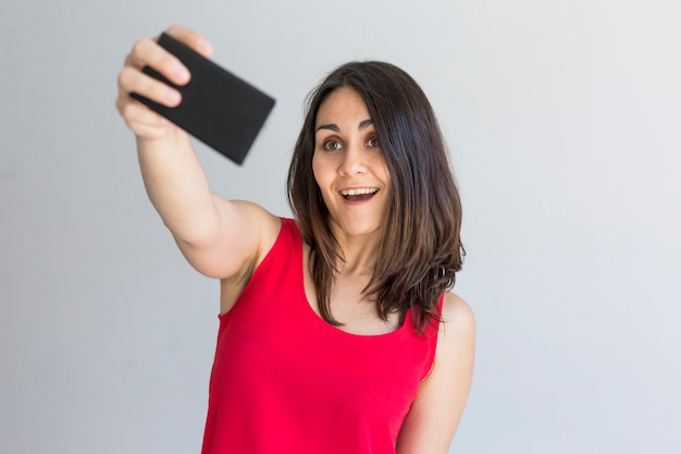Glückliche schönheit, die ein selfie mit intelligentem telefon über weiß nimmt