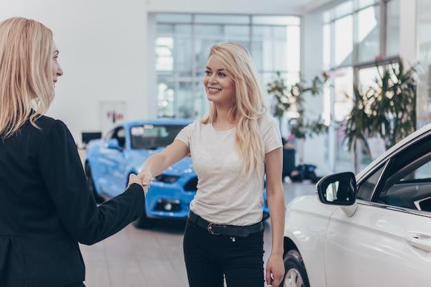 Glückliche schönheit, die hände mit autohändler rüttelnd lächelt, nachdem neues automobil gekauft worden ist