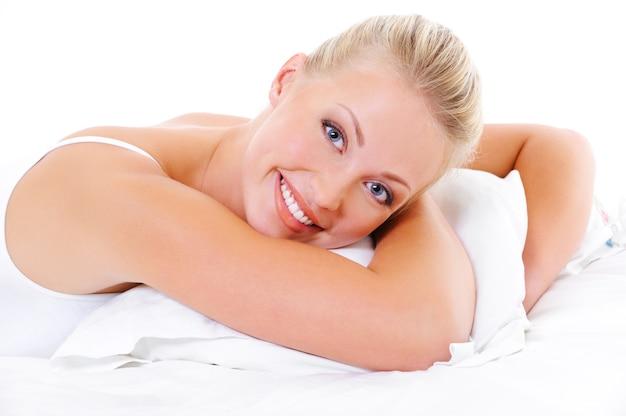 Glückliche schönheitsfrau mit zahnigem lächeln und gesunder haut, die auf bett und umarmungskissen liegt