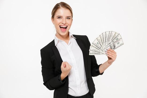 Glückliche schreiende blonde geschäftsfrau, die geld und über weiße wand hält