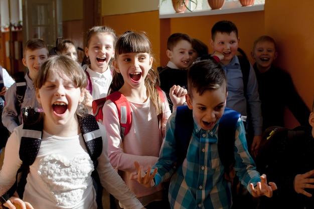 Glückliche schüler, die in den sommerferien aus dem klassenzimmer rennen