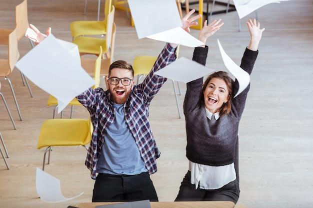 Glückliche schüler machen chaos in der bibliothek, indem sie papiere werfen