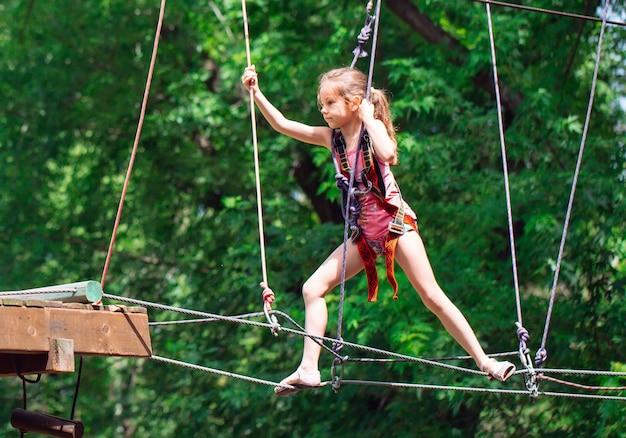 Glückliche schulfrau, die aktivität in einem kletterabenteuerpark an einem sommertag genießt,