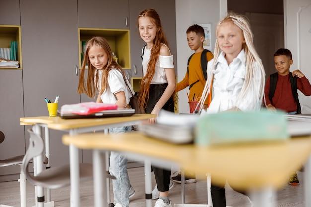 Glückliche schulkinder mit rucksäcken, die das klassenzimmer betreten