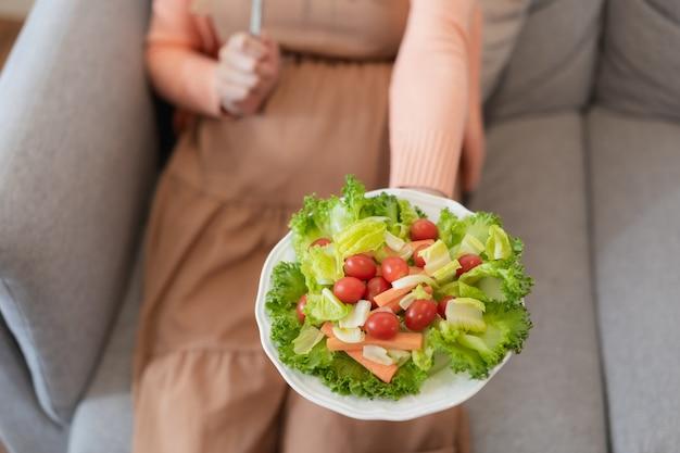 Glückliche schwangere asiatin, die gesundes lebensmittel des natürlichen gemüsesalats sitzt und isst und auf sofa sitzt