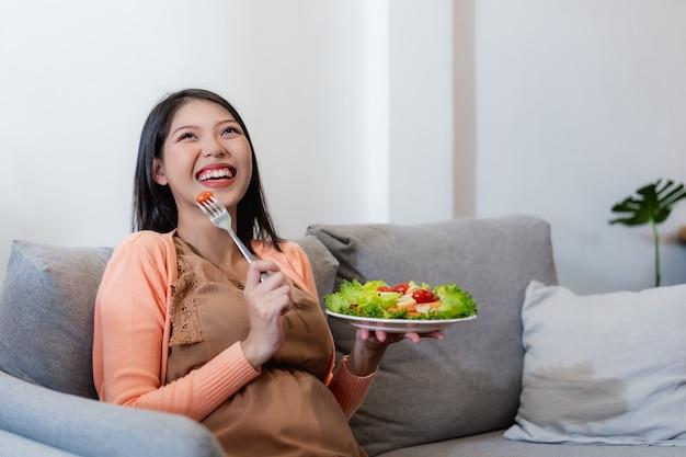 Glückliche schwangere asiatische frau, die gesundes essen des natürlichen gemüsesalats sitzt und isst und auf sofa sitzt