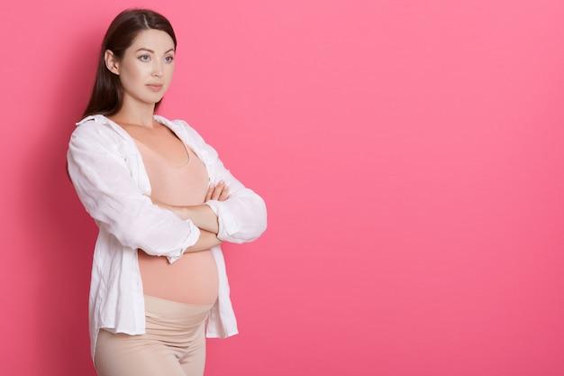 Glückliche schwangere dame, die mit verschränkten armen steht und zur seite schaut, hat ernsten blick