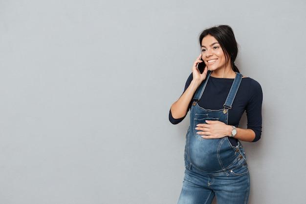 Glückliche schwangere dame, die per telefon spricht