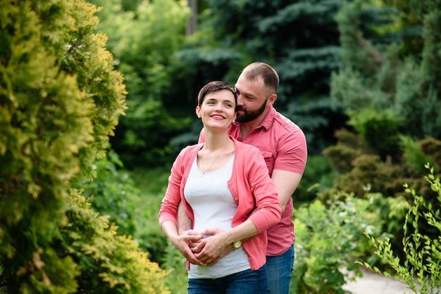 Glückliche schwangere familie geht in den park.