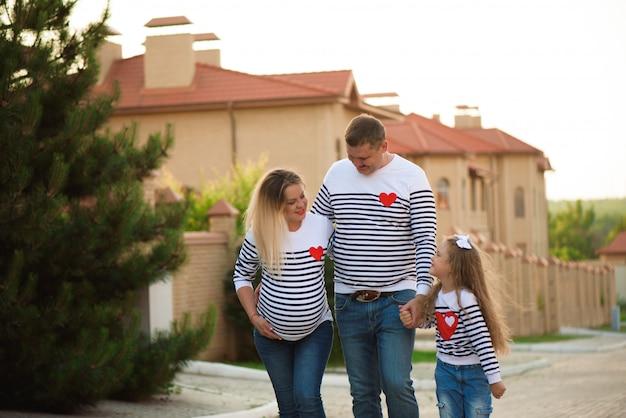 Glückliche schwangere familie mit dem kleinen mädchen, das gehende sommerzeit des spaßes hat.
