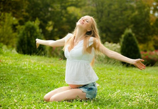Glückliche schwangere frau auf dem weichen gras