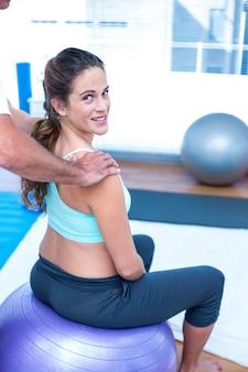 Glückliche schwangere frau, die entspannende massage an der turnhalle hat