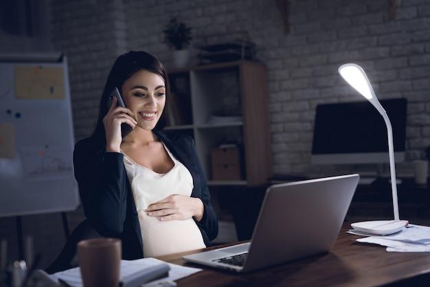 Glückliche schwangere frau, die im büro sprechend arbeitet