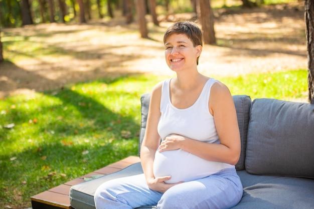 Glückliche schwangere frau, die im sommerpark sitzt