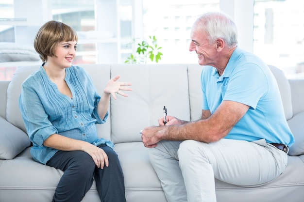 Glückliche schwangere frau, die mit gynäkologen spricht