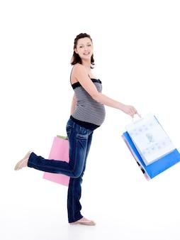 Glückliche schwangere frau, die nach dem einkaufen geht