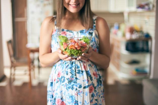Glückliche schwangere frau, die platte mit gemüse hält