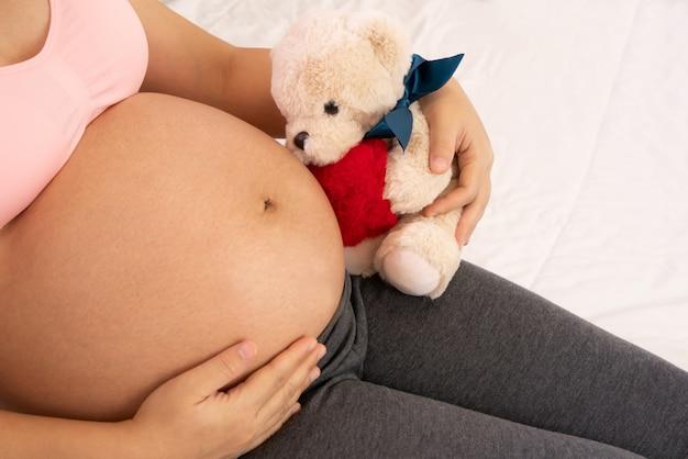Glückliche schwangere frau mit baby im schwangeren bauch
