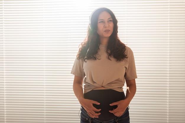 Glückliche schwangere frau mit dem lockigen haar, das musik in den kopfhörern hört, kopienraum.