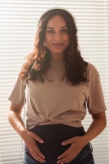 Glückliche schwangere frau mit dem lockigen haar, das musik in den kopfhörern hört