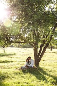 Glückliche schwangere frau mit ihrem ehemann bei sonnenuntergang